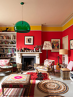 The red living room has a feature yellow-painted cornice and a central Victorian fireplace, furnished with a pair of retro armchairs and a green glass pendant lamp
