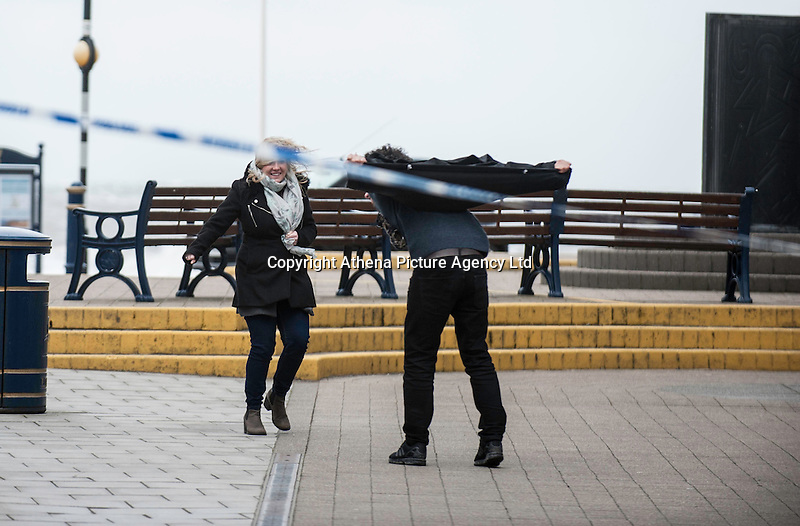 """WEATHER PICTURE WALES<br />Pictured: People struggle to walk against the strong wind in Aberystwyth, Ceredigion, Wales. Wednesday 02 March 2016<br />Re: Roads have been closed, homes left without power and tiles blown from roofs after Storm Jake brought wintry showers and high winds to Wales.<br />Yellow Met Office """"be aware"""" warnings of snow, ice and wind were issued for most of Wales for Wednesday morning.<br />Gusts - forecast to reach up to 70mph - caused roof tiles to fall and trees to be blown over in Aberystwyth, with roads closed as a precaution."""