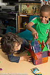 Preschool 3 year olds two boys playing together with plastic bears and construction made of magnetic blocks