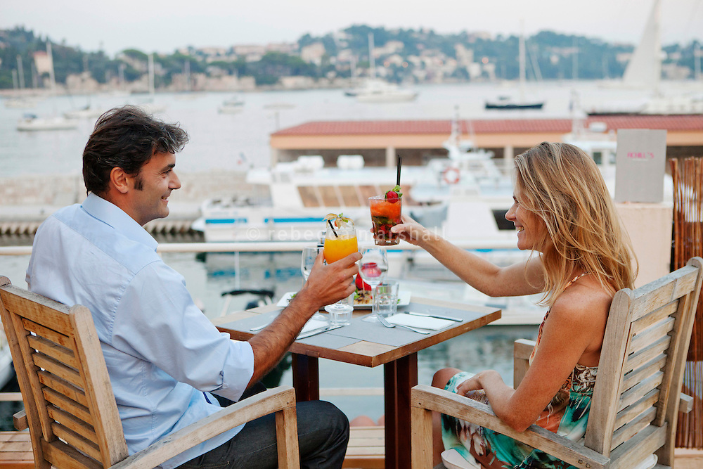 Pierre and Caroline drink cocktails on the rooftop terrace of Achill's restaurant, Villefranche-sur-Mer, France, 7 September 2012. Pierre drinks a 'Porte-Bonheur' (l'Lucky Charm') consisting of vodka, champagne and passion fruit juice, and Caroline drinks a strawberry mojito.