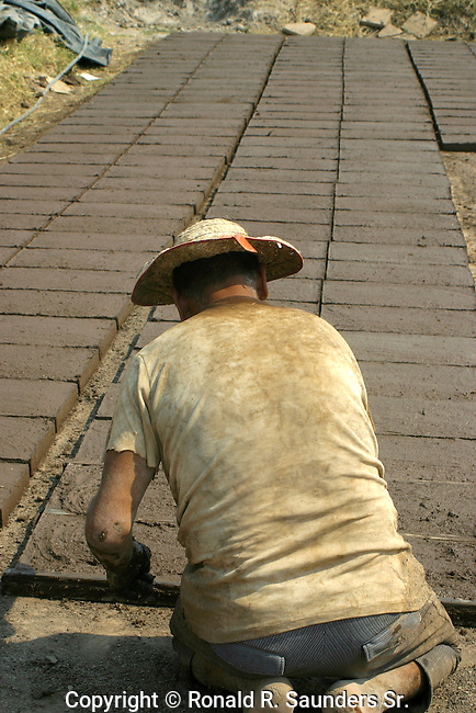 Poor Mexican man labors to create a brick platform<br /> (2)