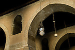 Cairo, Egypt -- Lamps and careful plasterwork decorate the arches and capitals within the historic ibn Tulun mosque.  Smaller arched openings are cut high in the walls of the arcades on the Qibla side of the mosque, both to admit light and to allow sound to travel unhindered (even slightly amplified) from the mihrab bay where the imam would deliver prayers and readings. © Rick Collier / RickCollier.com