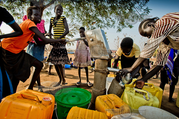 South Sudanese women and children fill jerry cans with water at a pump in Dzaipi transit centre. There are 24 water taps, in Dzaipi, one for every 1,354 refugees. In Dzaipi, 8.5 litres of water was available per person per day, while the emergency standard is 15 litres.