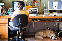 Woman sitting at her computer desk with her Golden Retriever lying at her feet