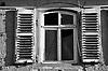 altes Fenster mit kaputter Scheibe und blauen Fensterläden mit abblätternder Farbe