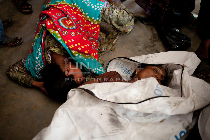 Bangladeshi woman mourn a relative  after a river ferry carrying more than 100 passengers capsized in the River Padma Sunday after being hit by a cargo vessel at Paturia, in Manikganj district, about 80 kilometers  northwest of Dhaka, Bangladesh. Feb. 22, 2015
