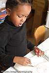 Education preschool 3-4 year olds art activity boy drawing with marker talking to himself vertical