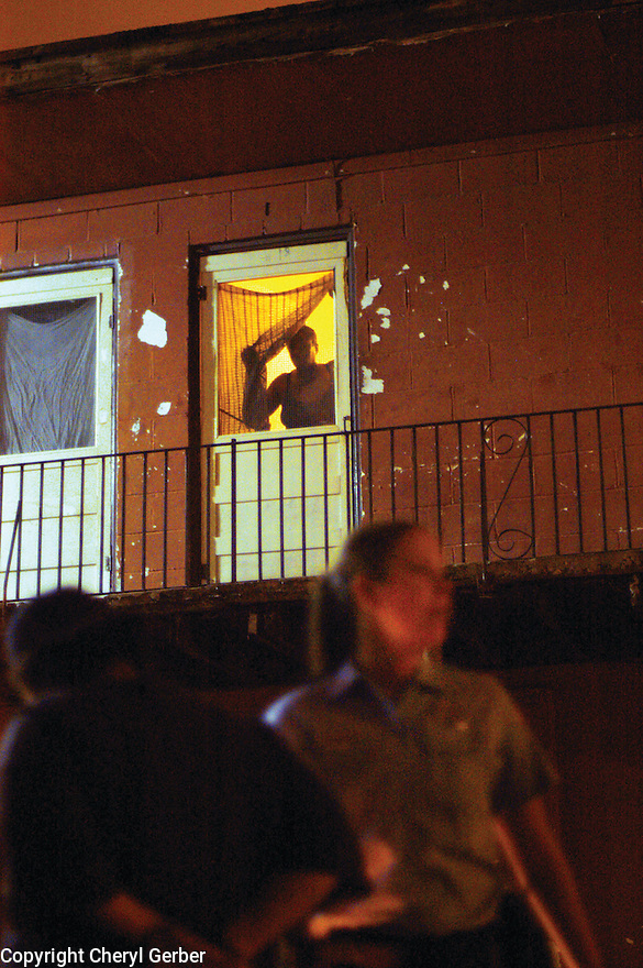 A  woman looks through window as police make an arrest in Central City, 2004