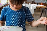 Suzhou, Jiangsu, China.  Little Girl Practicing Embroidery.