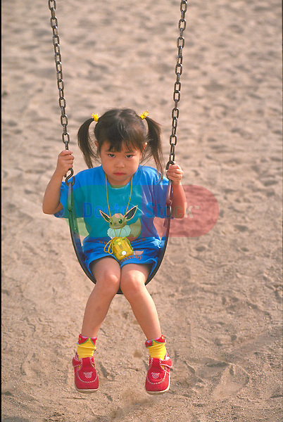 sad young girl swinging alone in park