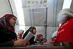 """Seventh-grade girls attend Arabic class at the school in Azaz Camp, just inside the Syrian border with Turkey, Feb. 26, 2013. A private charity donated the tents for the school, which has around 800 students between the ages of 6 and 16. Desks and other materials were salvaged from schools in Azaz village a few kilometers away. The school opened two months ago, and because there are so many children, they attend either a morning or an afternoon session, learning math, Arabic, English, and religion. Almost all of the teachers and staff are refugees and reside in the camp. The children come to school with special challenges--they may have psychological distress because of traumatic events or health problems due to poor living conditions in the camp, and some have not been in school for a long time and have to catch up to their grade level. """"We try everything to make them happy,"""" said a teacher, Abdul Razaq. According to administrators, this camp holds roughly 9,000 to 10,000 internally displaced persons (IDP's). Two meals per day are provided by a Turkish humanitarian organization, and Qatar Red Crescent provided tents. There is very little electricity, and no running water. There is also a refugee camp on the Turkish side of the border, but it is full. The UN Refugee Agency has reported a sharp increase in refugees fleeing Syria for neighboring countries in the first months of 2013."""