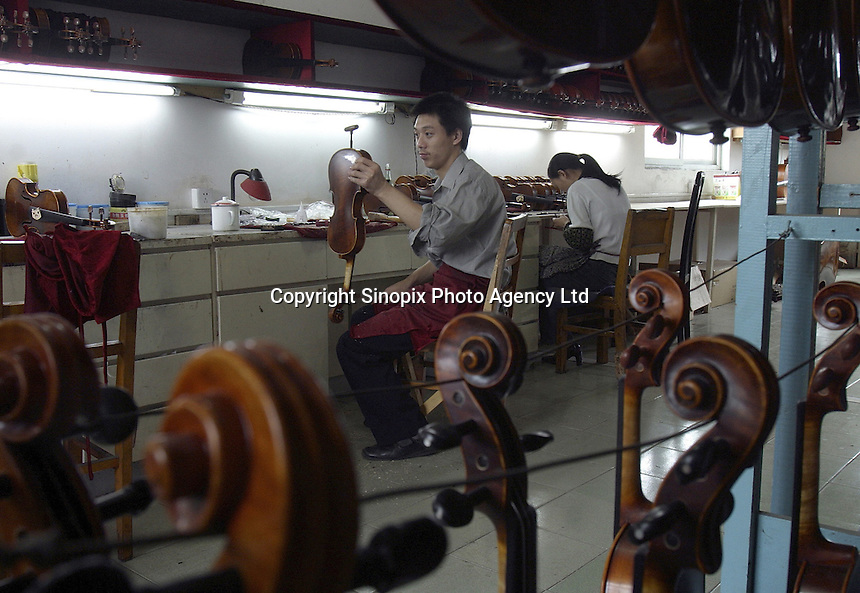 A Chinese craftsman makes some final adjustments to a violin at the Shanghai Wellsound-Tianyin Violin Factory  in Shanghai, China. Started in 1992 by a family with four generations of music instruments making experience, the company exports most of its high-end and hand crafted string instruments overseas. China supplies over 90% of the world's high-end music instruments..13-SEP-04