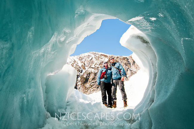 Happy tourists pose for picture at a beautiful ice cave on the Franz Josef Glacier - Westland National Park, West Coast, New Zealand
