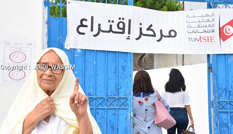 TUNIS, TUNISIA - SEPTEMBER 15: Tunisian woman shows her inked finger after casting her vote at a polling station during the presidential elections in Tunis, Tunisia on September 15, 2019