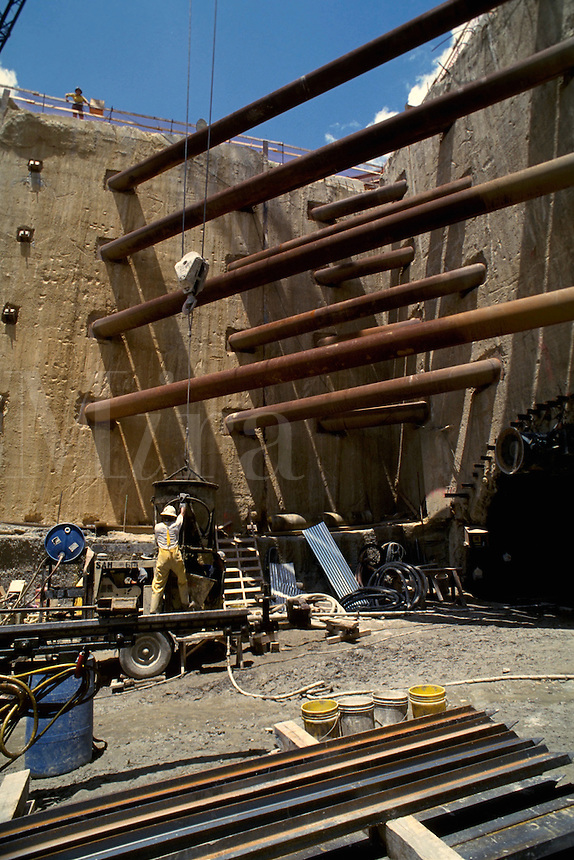 Heavy construction site shows stabilizers holding up the walls of a sub-surface entrance to a tunnel being built. A crane hoists a large bucket of cement to a worker to empty for use in the tunnel.