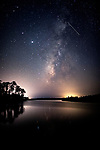 A meteor from the Orionids Meteor shower streaks through the Milky Way over Cash Creek which flows out of Tate's Hell swamp into Apalachicola Bay.  The horizon  lights are from Eastpoint on the left and Apalachicola.  The main galactic core of the Milky Way will drop below the horizon line in the northern hemisphere the end of October through April so get out in the dark and enjoy it why you can.