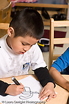 Education preschool 4 year olds art activity boy drawing recognizable shape with markers vertical