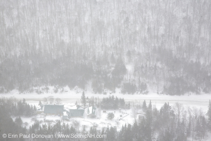 Kinsman Notch (Route 112) from the Dilly Cliffs Trail in the White Mountains, New Hampshire USA during a snow storm in the winter months. Buildings of the Lost River Reservation are in view.
