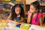 Education Elementary School Kindergarten mathematics using manipulatives, two girls at work