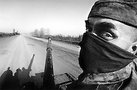 A Russian soldier advancing with his tank down an isolated road in the Chechen countryside...