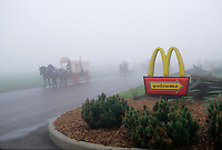 An annual reenactment of a westering caravans during the Pike festival, although the first settlers didn't stop for fast food coffee along their route.<br /> Wagons and horses roll out of McDonalds in a thick fog as the wagon train heads west.
