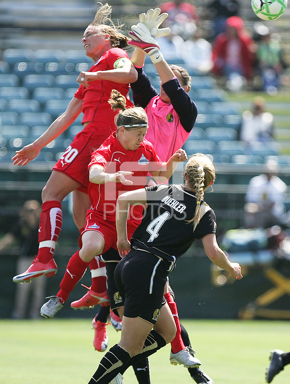 Abby Wambach (20) scores on the header over FC Gold Pride Goalie Nicole Barnhart (pink) above Rebecca Moros (center) and Rachel Buehler (4). Washington Freedom defeated FC Gold Pride 4-3 at Buck Shaw Stadium in Santa Clara, California on April 26, 2009.