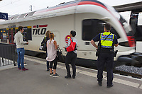 Switzerland. Canton Ticino. Lugano. Railway station. A TILO train enters the station while a police officer from TPO (Transport Police) and some passengers stand on the platform. TPO (Transport Police) is the Swiss Federal Railways Police. Swiss Federal Railways (German: Schweizerische Bundesbahnen (SBB), French: Chemins de fer fédéraux suisses (CFF), Italian: Ferrovie federali svizzere (FFS)) is the national railway company of Switzerland. It is usually referred to by the initials of its German, French and Italian names, as SBB CFF FFS. TILO (Treni Regionali Ticino Lombardia) creates efficient train connections between the towns in the canton Ticino. 12.06.2017 © 2017 Didier Ruef