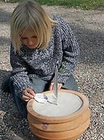 Kinder bauen eine Sonnenuhr, in einen mit Sand befüllten Blumentopf wurde eine Feder gesteckt, deren Schatten die Uhrzeit zeigen soll, die Uhrzeiten wurden Rand aufgetragen, nun werden wichtige Termine auf Muschelschalen geschrieben und auf die entsprechenden Zeit gelegt
