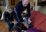 Olga Batiounina, left, and her husband William Massart, right, secure boots to their daughter Sandra Massart, 10, preparing to stand the girl up for strength therapy at the family's apartment in Durham, NC, USA, on Tuesday, Feb. 14, 2012.  Sandra Massart is being treated at Duke University Hospital in Durham, NC, for MLD, a degenerative condition.  Photo by Ted Richardson