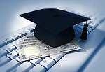 Close-up of mortarboard with Indian currency on keyboard representing software graduation