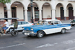 Havana, Cuba; a classic blue and white 1958 Chevy Bel Air driving along the Paseo de Marti past the Saratoga Hotel