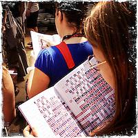 """Fusion-Festival 2014 auf dem Gelaende des Kulturkosmos e.V. in Laerz/Mecklenburg-Vorpommern.<br /> Bis zu 65.000 Menschen kommen jaehrlich fuer 5-6 Tage  zur """"Fusion"""" nach Laerz.<br /> Das linke Festival, was von den Besuchern und Machern scherzhaft auch als """"Ferienkommunismus"""" bezeichnet wird, ist eine Mischung aus Techno-Dancefloors, Theater und Live-Auftritten von politischen Bands.<br /> Die Karten fuer dieses Festival sind nur ueber die Fusion-Internetseite per Losverfahren zu kaufen. Nur ca. jede dritte bis vierte Anmeldung fuer eine Karte hat Erfolg.<br /> Im Bild: Festivalbesucherinnen studieren das Programm. Bei mehreren hundert Acts kann schnell der Ueberblick verloren gehen.<br /> 27.6.2014, Laerz<br /> Copyright: Christian-Ditsch.de<br /> [Inhaltsveraendernde Manipulation des Fotos nur nach ausdruecklicher Genehmigung des Fotografen. Vereinbarungen ueber Abtretung von Persoenlichkeitsrechten/Model Release der abgebildeten Person/Personen liegen nicht vor. NO MODEL RELEASE! Don't publish without copyright Christian-Ditsch.de, Veroeffentlichung nur mit Fotografennennung, sowie gegen Honorar, MwSt. und Beleg. Konto: I N G - D i B a, IBAN DE58500105175400192269, BIC INGDDEFFXXX, Kontakt: post@christian-ditsch.de<br /> Urhebervermerk wird gemaess Paragraph 13 UHG verlangt.]"""
