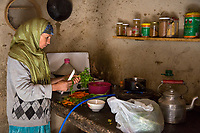 Dades Gorge, Morocco.  Middle-aged Berber Woman Preparing Dinner in her Kitchen.