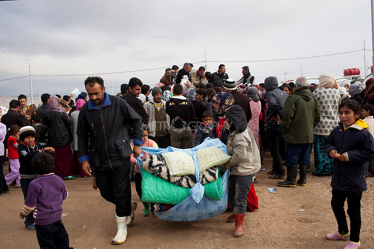 DOMIZ, IRAQ: Syrian refugees carry recently donated pillows and blankets in the Domiz refugee camp in the Kurdish region of northern Iraq...The semi-autonomous region of Iraqi Kurdistan has accepted around 60,000 refugees from war-torn Syria. Around 20,000 refugees live in the Domiz camp which sits 60 km from the Iraq-Syria border...Photo by Younes Mohammad/Metrography