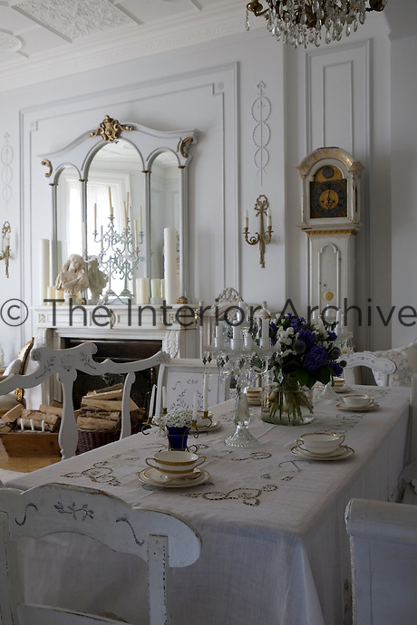 The dining area of the open-plan living/dining room has a long dining table covered with an antique linen cloth