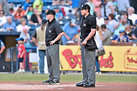 Umpires Zach Neff (left) and Sam Burch (right) before the South Atlantic League game between the Greenville Drive and the Asheville Tourists at McCormick Field on April 13, 2017 in Asheville, North Carolina. The Tourists defeated the Drive 3-1. (Tony Farlow/Four Seam Images)