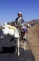 Yemen, a young boy  rides his donkey wearing his jambiya dagger