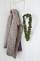 A homemade heart of moss hangs beside a warm jacket on a hook behind a simple door in the hallway