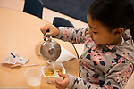 Education Preschool classroom scenes 4-5 year olds girl pouring own milk at breakfast