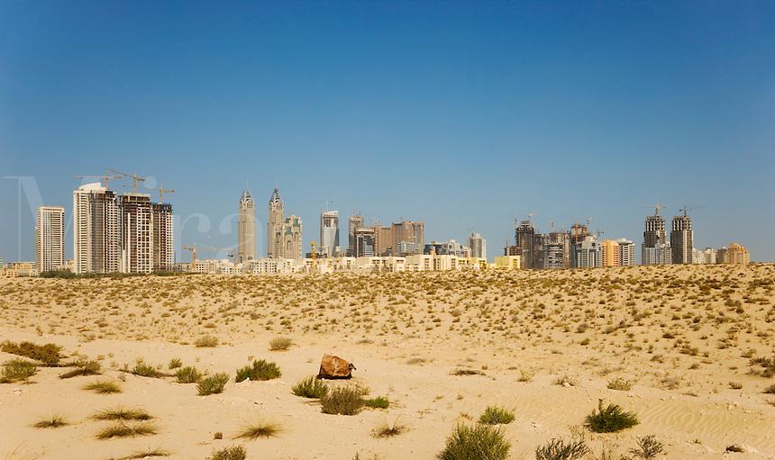 Dubai rises from the desert.  Skyline looking across the desert towards the Greens community..