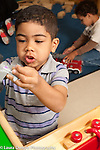 Education Preschool 3-4 year olds boy playing with toy airplane, talking to himself