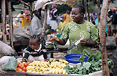 Lolgorian, Kenya. Smiling women selling fruit and vegetables with her daughter at the market.