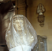 A marble bust is wrapped in polythene to protect it from dust during renovations