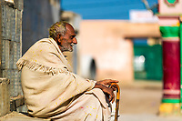 Old man seated with his cane, with the colorful Sri Kugal Kishore Ji temple in the background in Vrindavan, near Mathura Uttar Pradesh, India
