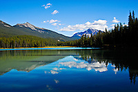 Clouds, blue sky, mountains and forest are reflected in the calm waters of Wabasso Lake in Jasper National Park Alberta Canada