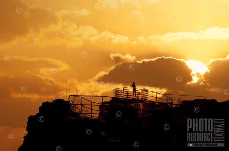 A woman runner enjoying the sunset and view with the sun dropping below the clouds.