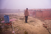 A day wage labourer waits outside the make-shift brick house at a construction site on a cold winter morning in Ghaziabad, Uttar Pradesh, India. Local volunteers from the Rotary International, WHO and the Government of India carry on with house to house survey at high risk migrant populations, mostly staying at construction sites.
