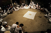 Recife, Pernambuco State, Brazil. Candomble religious ceremony; people in white surround food offering.
