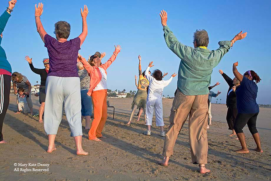 Mature Caucasian and African American women dance and exercise on Playa del Rey Beach in Los Angeles, California
