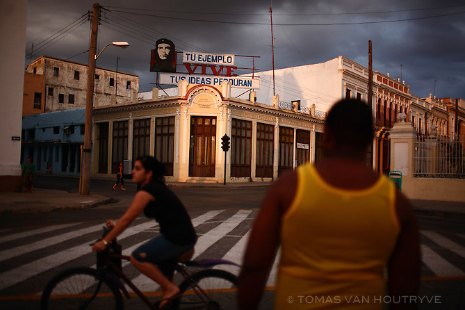 Cubans pass through the central square (Plaza Jose Marti) of Cienfuegos near a propaganda sign of Ernesto Che Guevara in Cuba on 15 March 2009.
